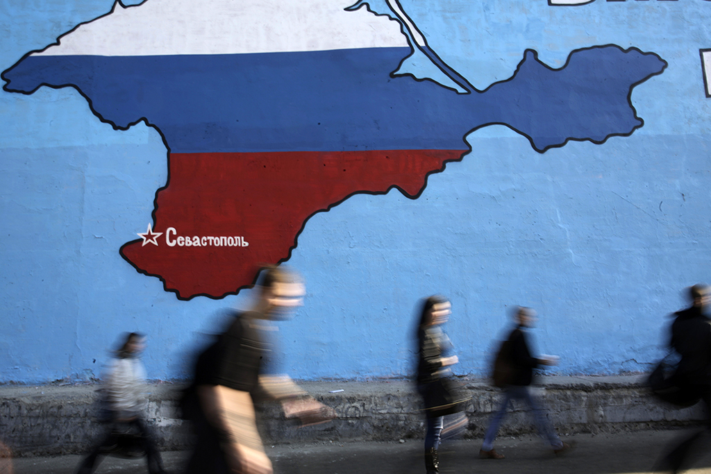 """People pass a mural showing a map of Crimea in the Russian national colours on a street in Moscow March 25, 2014. NATO's top military commander said on Sunday Russia had built up a """"very sizeable"""" force on its border with Ukraine and Moscow may have a region in another ex-Soviet republic, Moldova, in its sights after annexing Crimea. The map shows the location of the city Sevastopol. REUTERS/Artur Bainozarov (RUSSIA - Tags: POLITICS CIVIL UNREST TPX IMAGES OF THE DAY) - RTR3IH3Z"""
